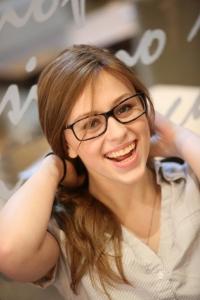 Kea smiling holding her hair